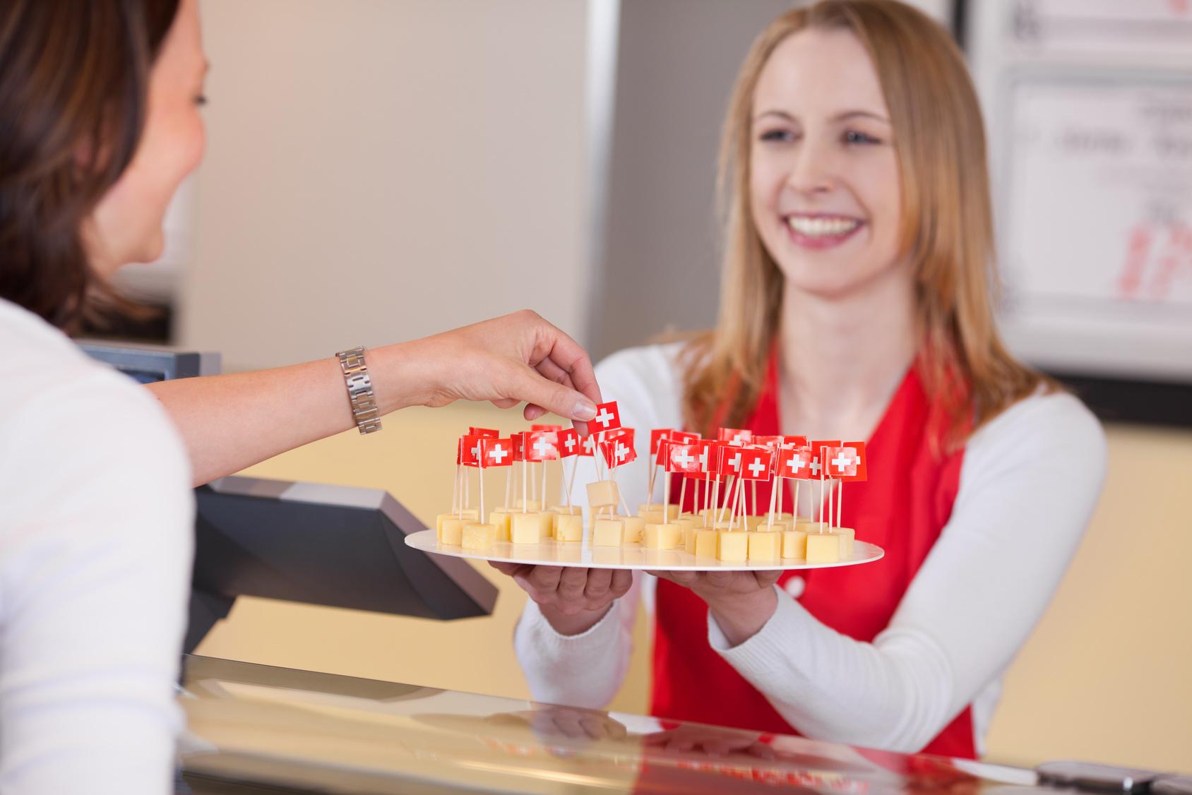 freundliche verkuferin bietet kse zum probieren an