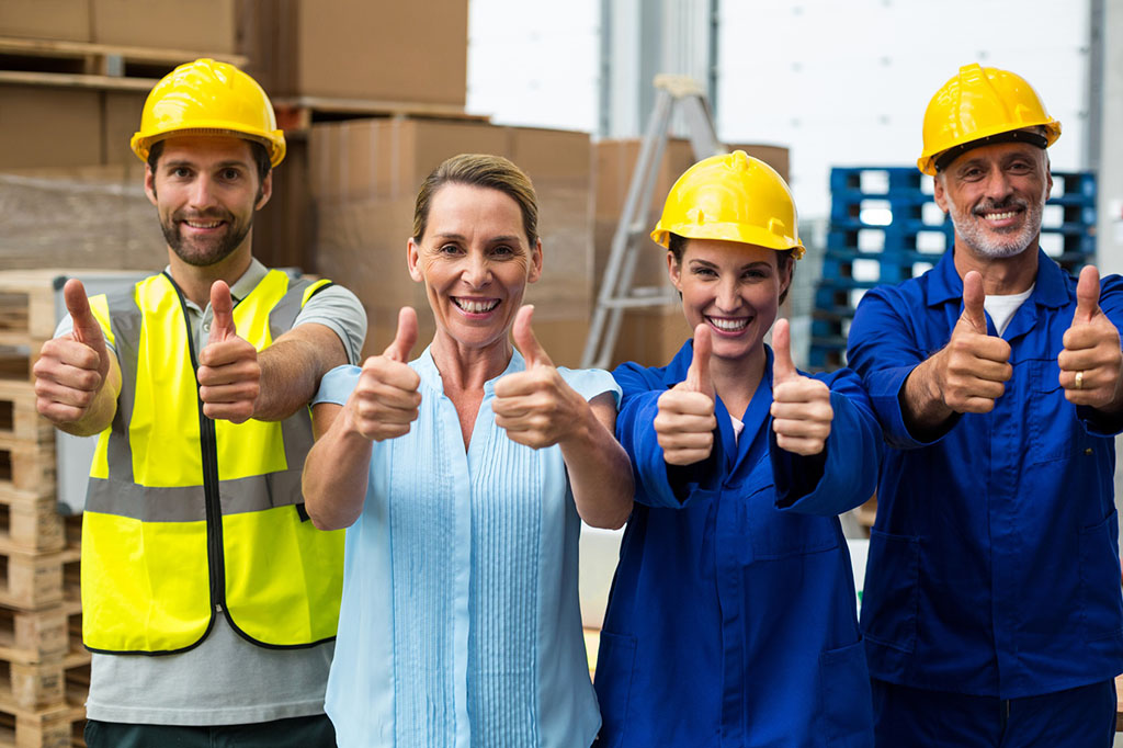 Portrait of warehouse manager and worker showing thumbs up